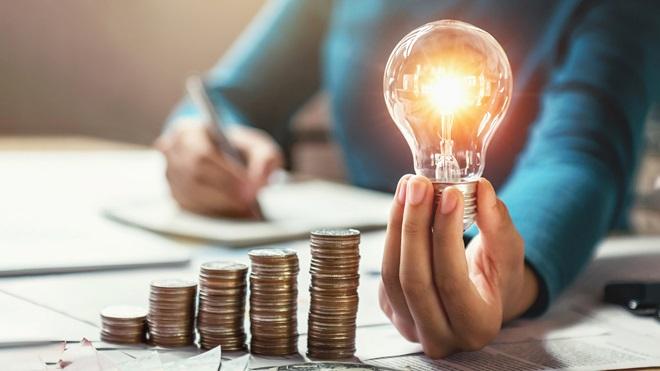 mano-monedas-bombilla-ahorro-energia