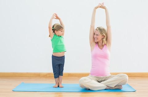 Niño y mujer haciendo yoga