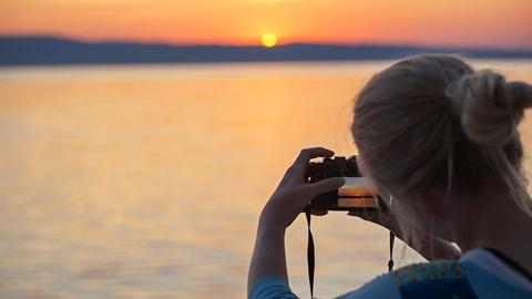 Mujer fotografiando el atardecer con cámara compacta